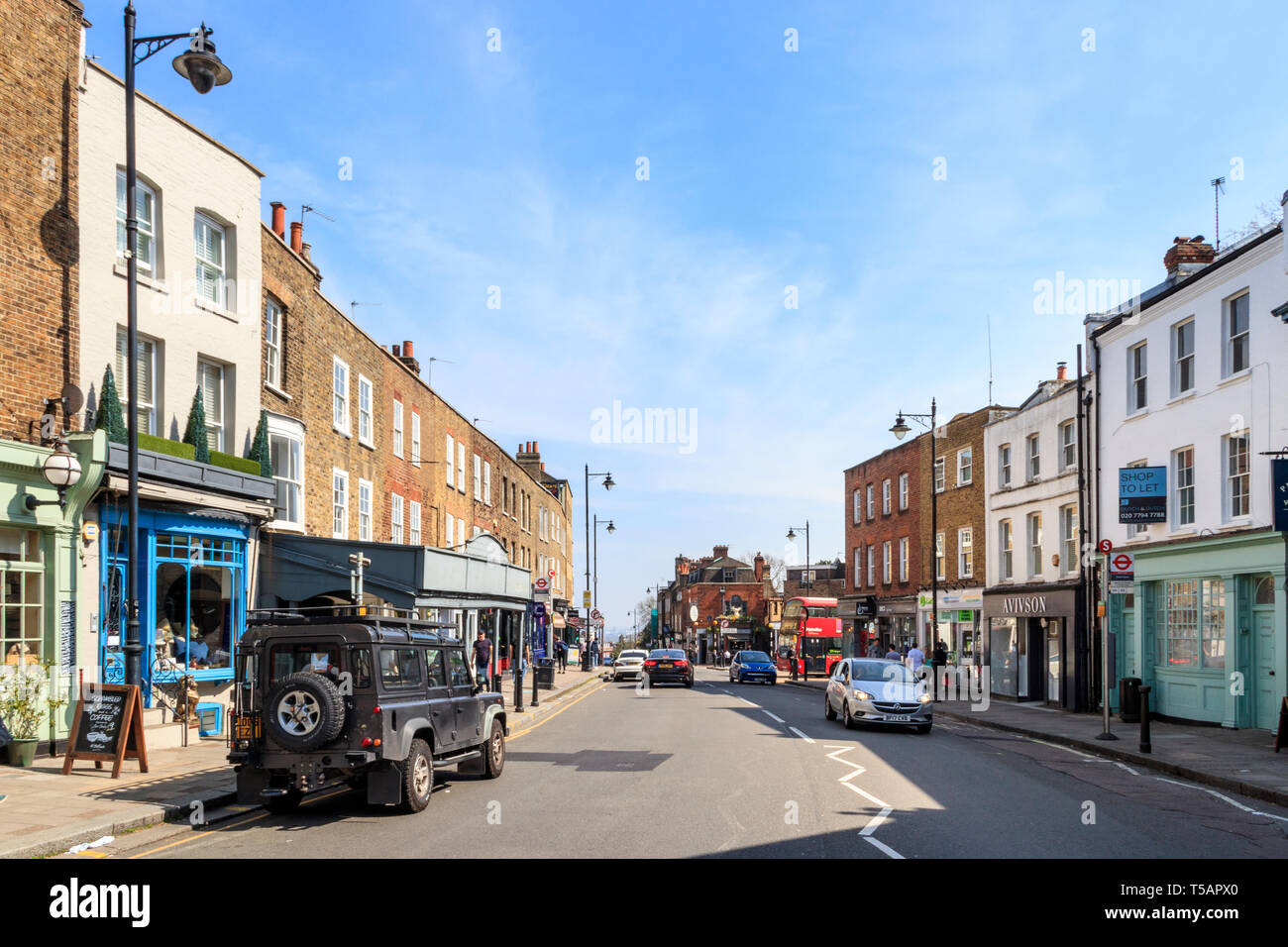 A view view south along the High Street on a warm and sunny Easter weekend, Hoghgate Village, London, UK - Stock Image