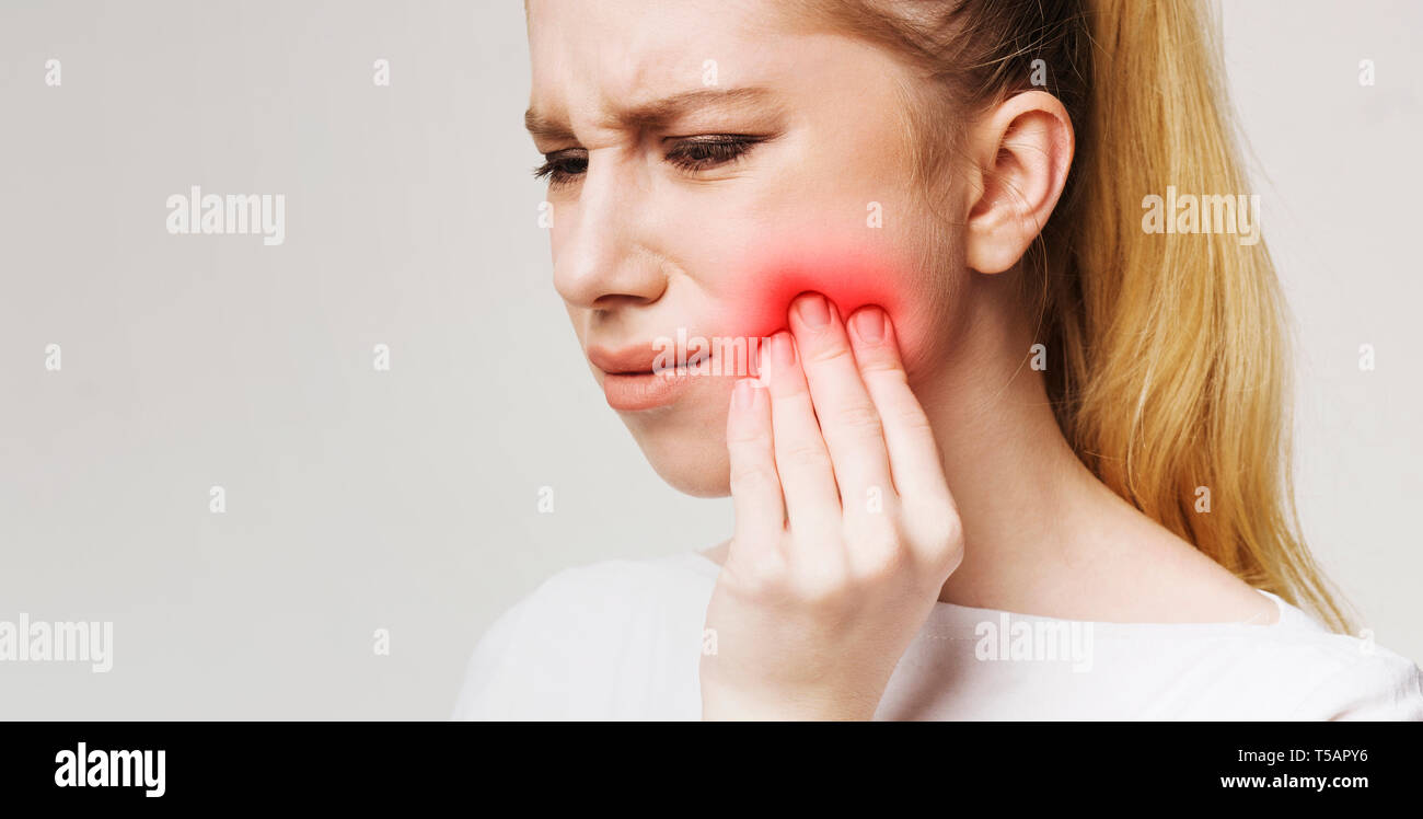 Frustrated young woman with toothache touching her cheek - Stock Image