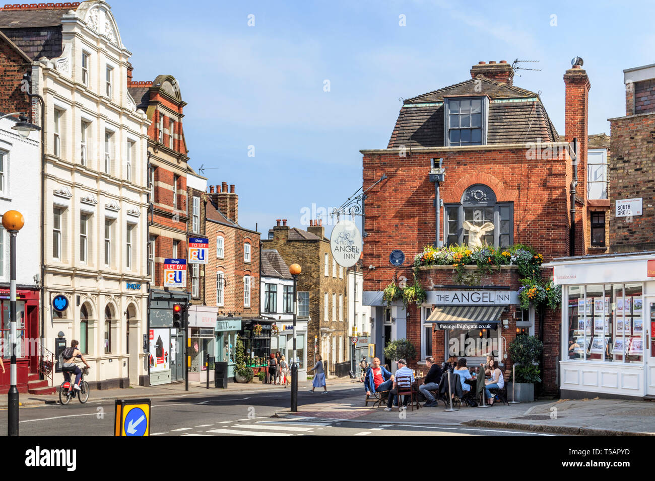 Customers drinking outside the historic Angel Inn in Highgate Village, London, UK, on a warm and sunny Easter weekend - Stock Image