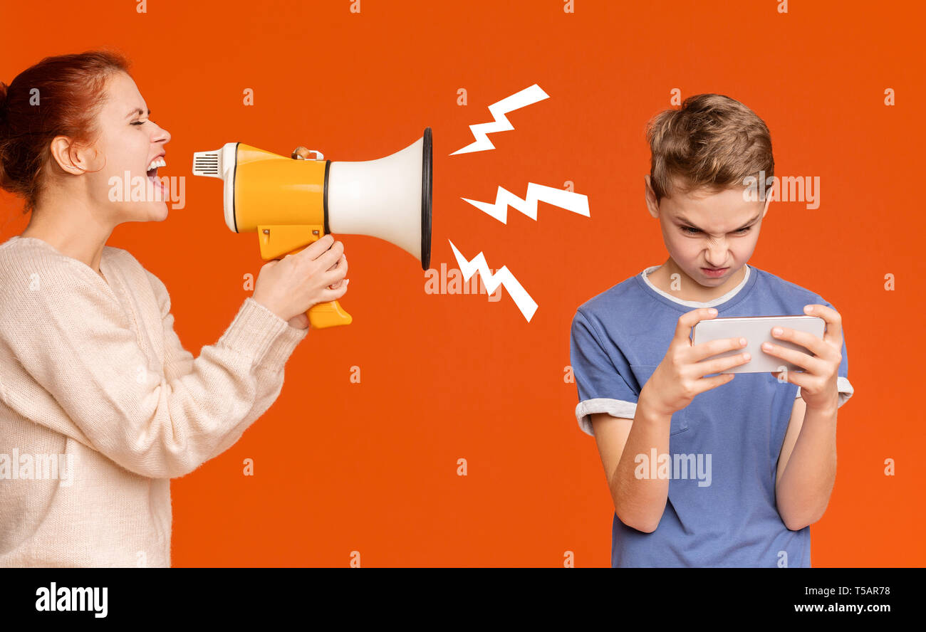 Gadget addicted boy playing mobile games on cellphone - Stock Image