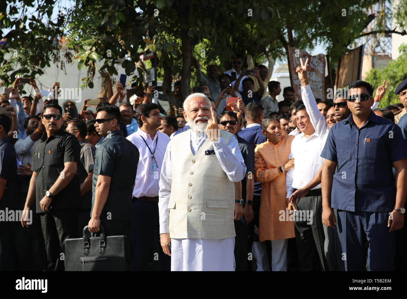(190423) -- AHMEDABAD, April 23, 2019 (Xinhua) -- Indian Prime Minister Narendra Modi (C) displays his inked finger after casting his vote at a polling station in Ahmedabad city of India's western state Gujarat on April 23, 2019. Indian Prime Minister Narendra Modi cast his vote in Ahmedabad city on Tuesday, which saw the third phase of the ongoing parliamentary elections. The third phase of the polling of votes in India's 17th general elections is the biggest among all the seven phases. The first two phases took place on April 11 and April 18 respectively, while the last phase is slated t - Stock Image