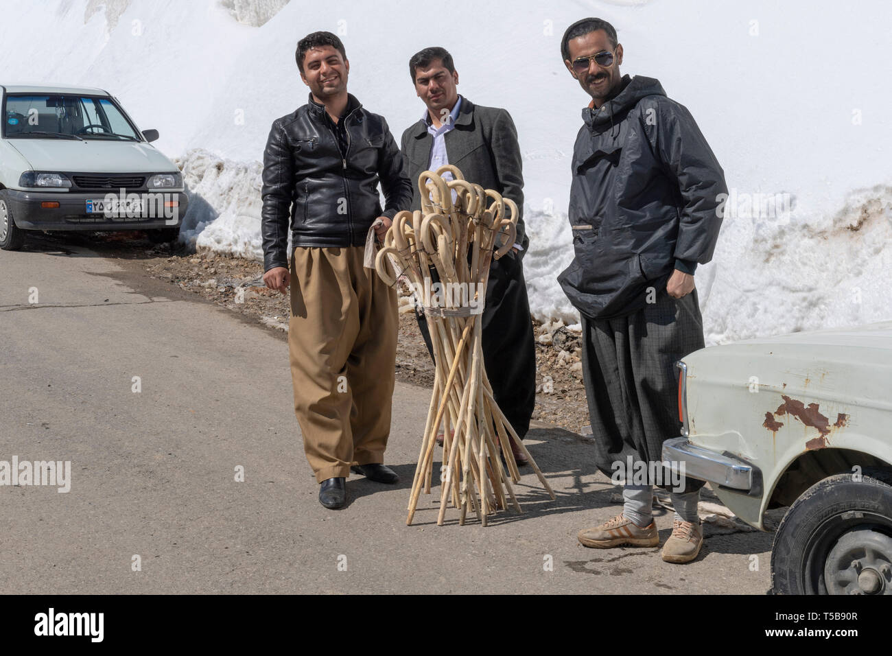 Men Selling Canes To Couriers To Help Them Walk To Iraq In The Snow In Winter, Uraman Valley, Kurdistan Province, Iran - Stock Image