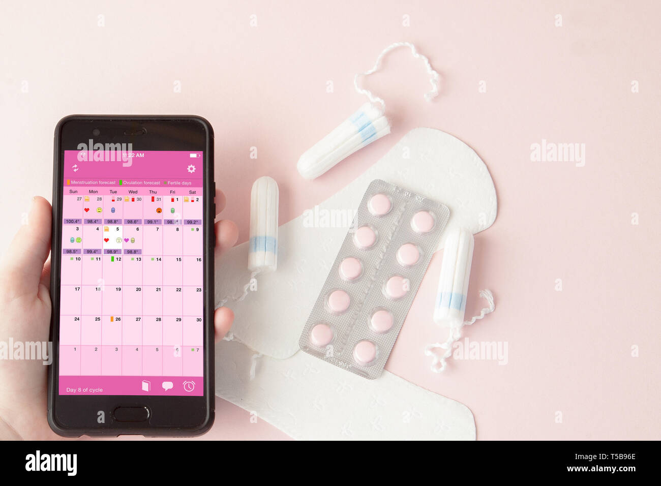 Tampon, feminine, sanitary pads for critical days, feminine calendar, pain pills during menstruation on a pink background. Tracking the menstrual - Stock Image