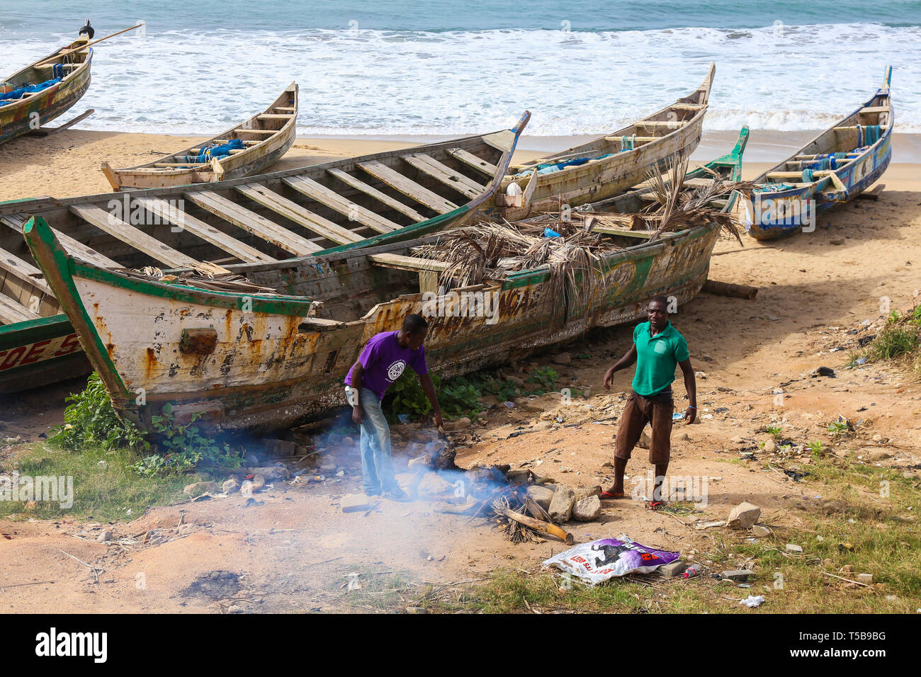 Two men cook a dog on the beach in Cape Coast, Ghana. - Stock Image