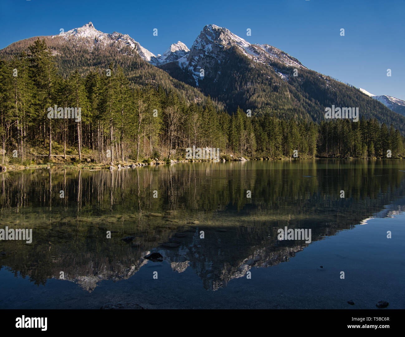 The partly still snow-covered mountains are reflected in the mountain lake. - Stock Image