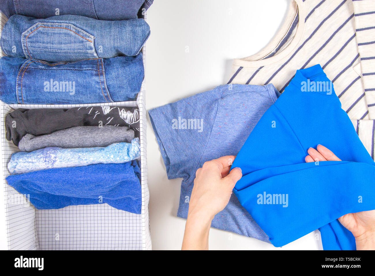 Woman hands tidying up kids clothes in basket. Vertical storage of clothing, tidying up, room cleaning concept - Stock Image