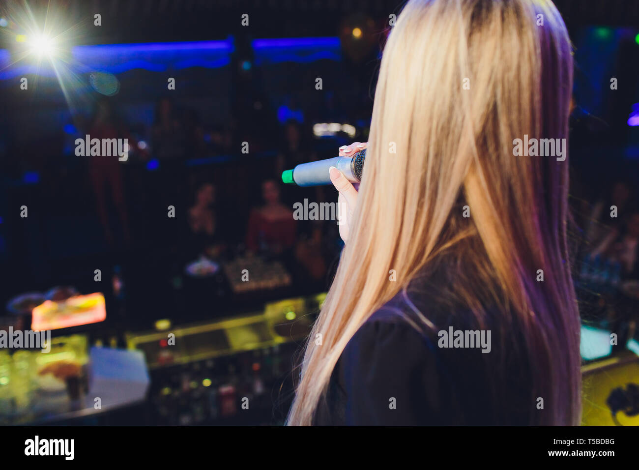 The female student is holding the black wireless microphone in the left hand and do the public speaking with blurred background. - Stock Image