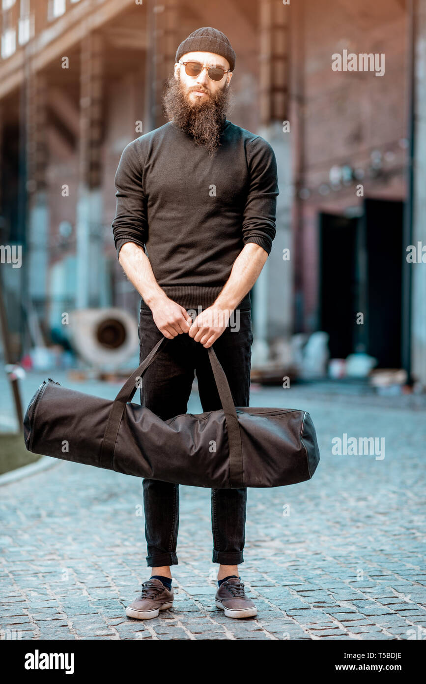 Portrait of a serious bearded man as a killer dressed in black tight clothes holding bag with weapons outdoors on the industrial background - Stock Image