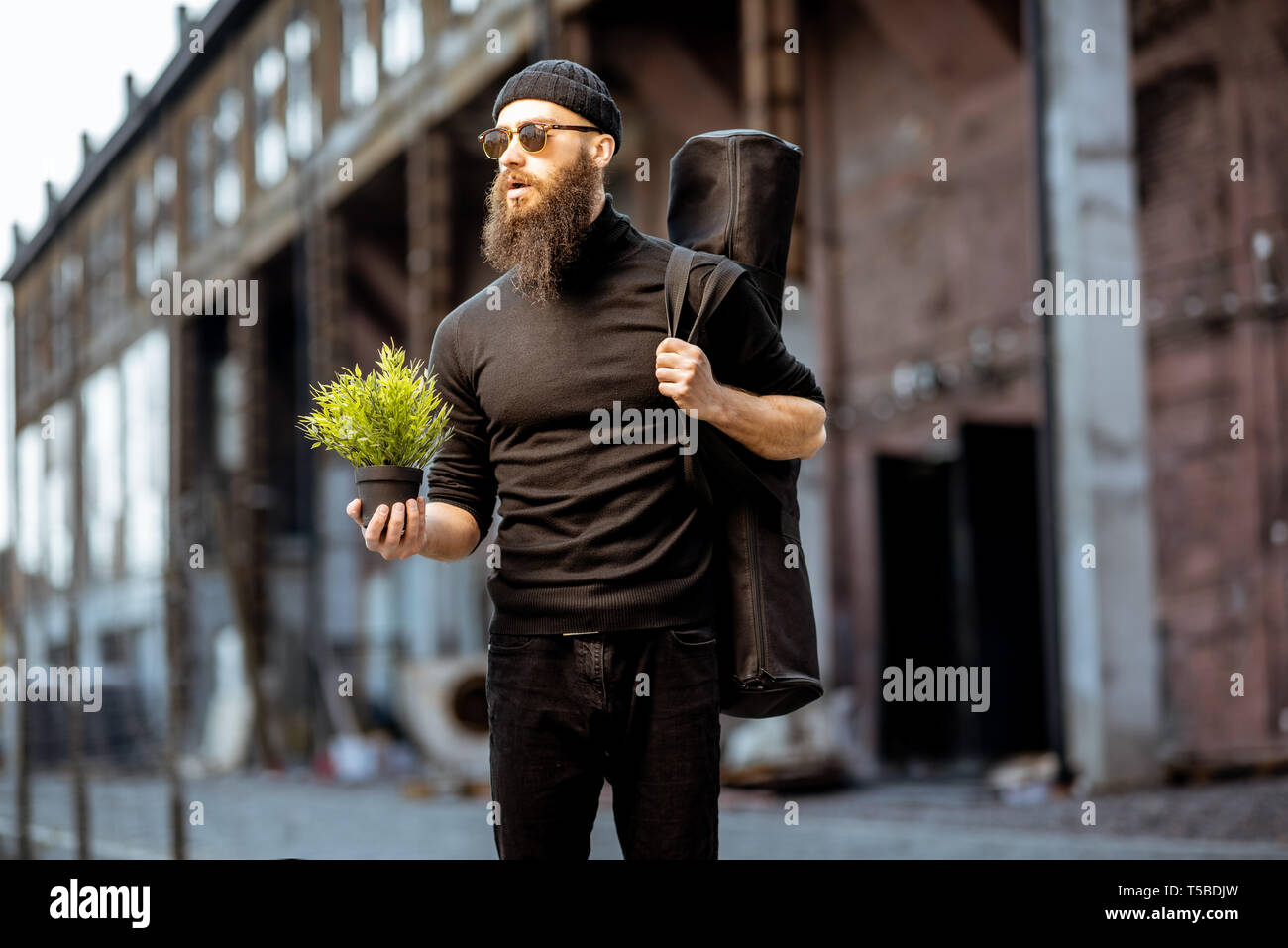 Portrait of a serious bearded man as a killer dressed in black tight clothes holding flower pot and bag with weapon outdoors - Stock Image