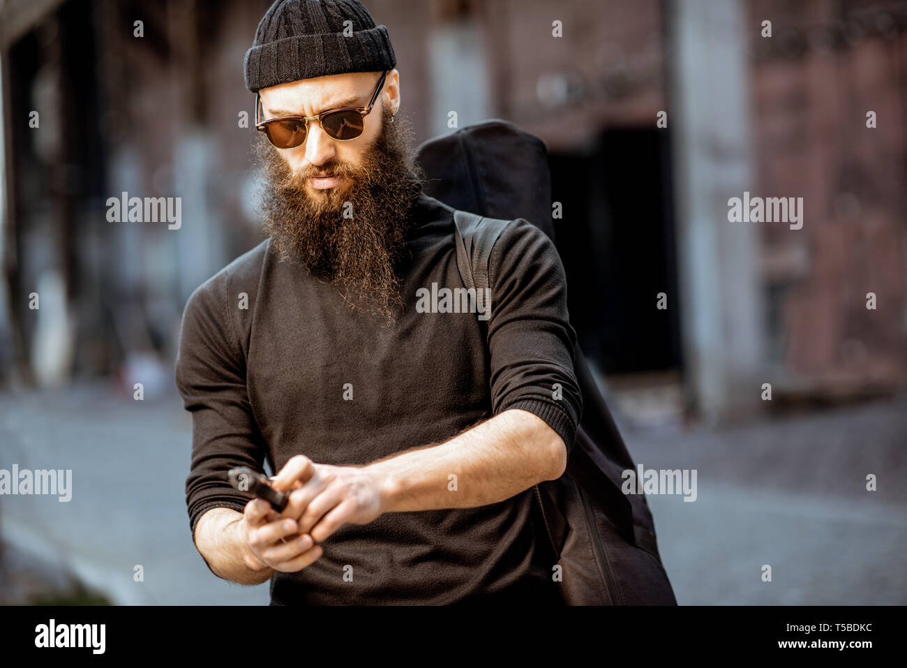 Serious bearded man dressed in black tight clothes as a killer standing with handgun outdoors on the industrial urban background - Stock Image