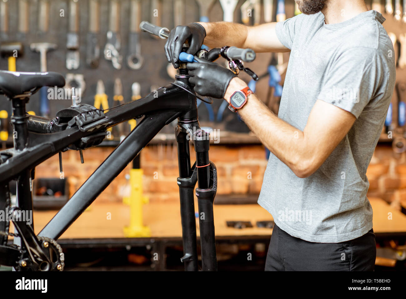 Man removing steering wheel from the bicycle at the workshop Stock Photo