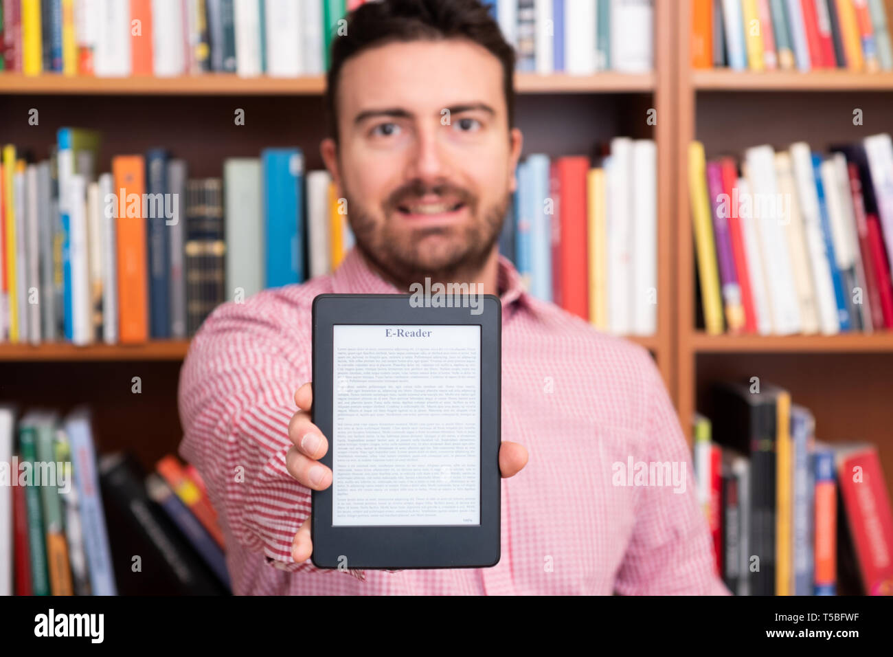 Holding in hands a modern ebook reader and paper books in the background - Stock Image