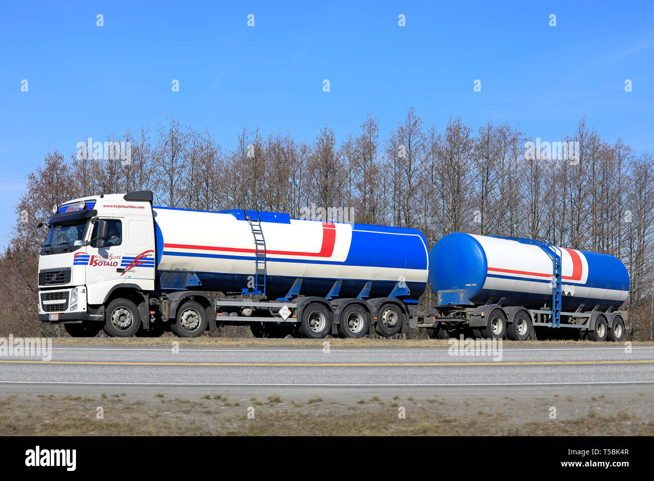 Forssa, Finland - April 6, 2019: Colorful Volvo FH 540 tank truck of Kuljetusliike Aarni Isotalo Oy at speed on highway ramp on a day of spring. - Stock Image