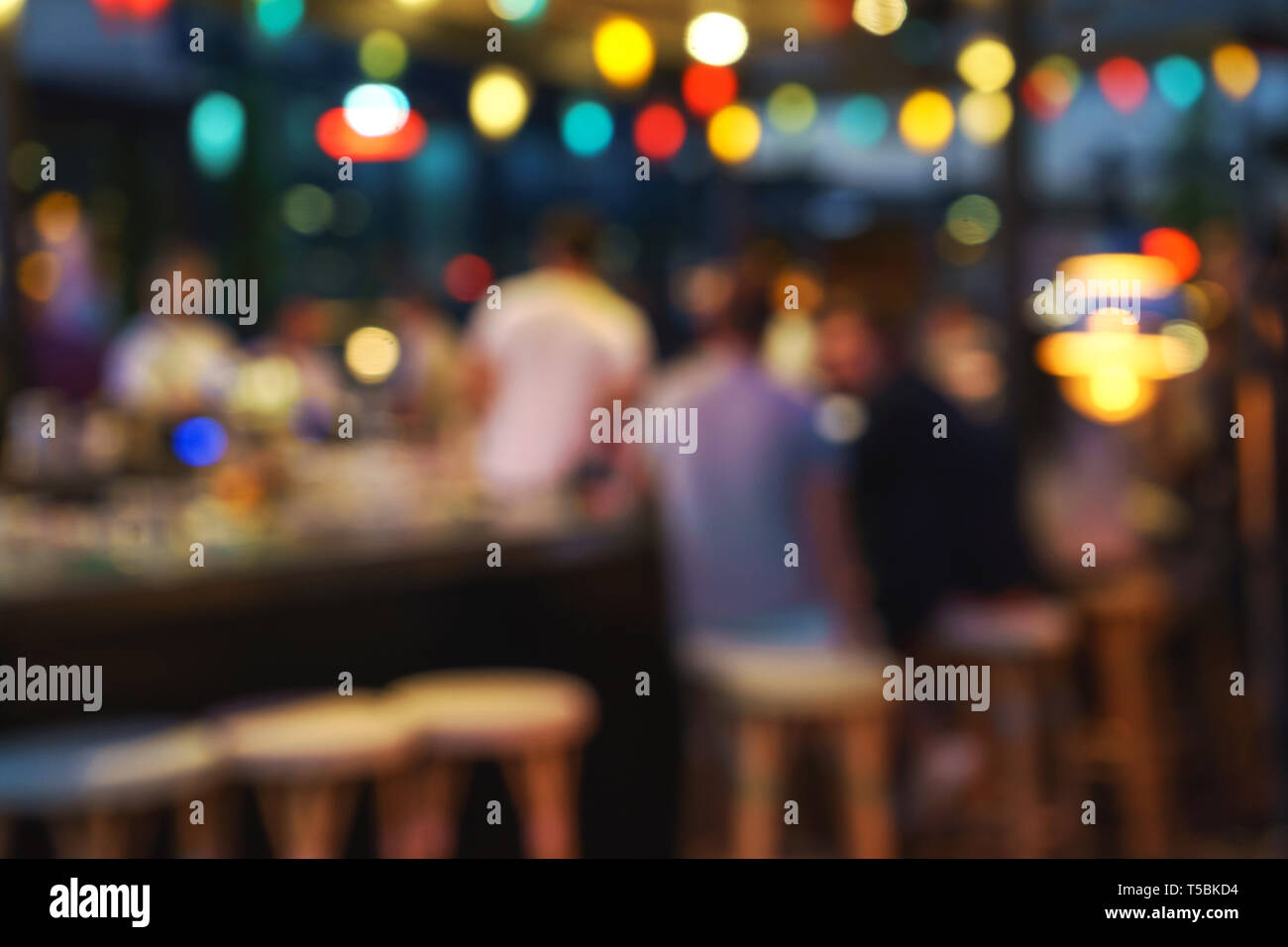 Blurred background of customer sitting at restaurant, bar or night club, with bokeh. - Stock Image