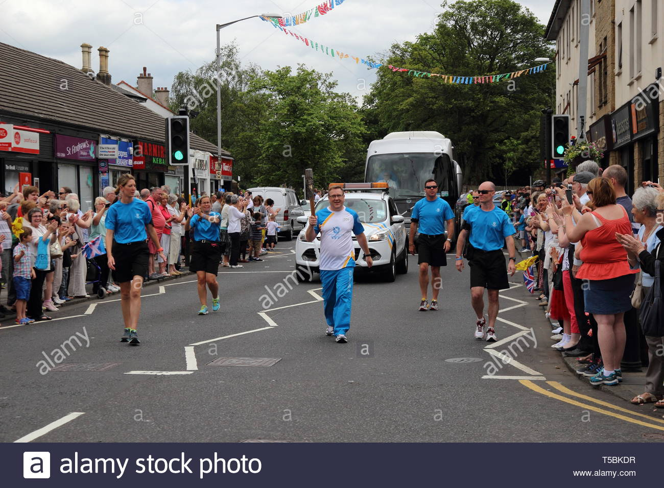 The Queen's Baton Relay for the Glasgow Commonwealth Games 2014 arrives in the East Kilbride village, South Lanarkshire, Scotland, UK. - Stock Image
