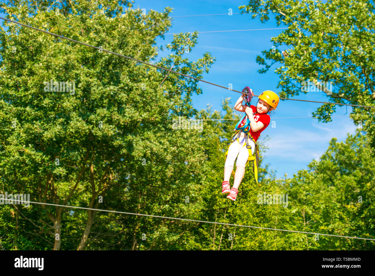 Little brave caucasian girl using a zip line. - Stock Image