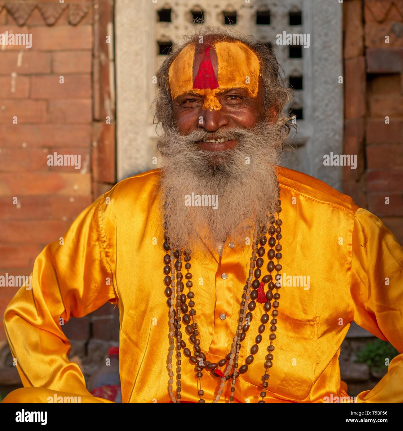TILGANGA, KATHMANDU, NEPAL - APRIL 2, 2019: one sadhu al dressed in silky saffron yellow clothing - Stock Image