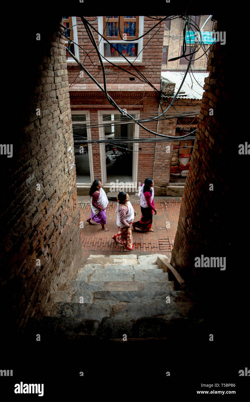 BHAKTAPUR, NEPAL - APRIL 5, 2019: Three women wearing traditional clothes walking in a narrow street, seen from a dark porch - Stock Image