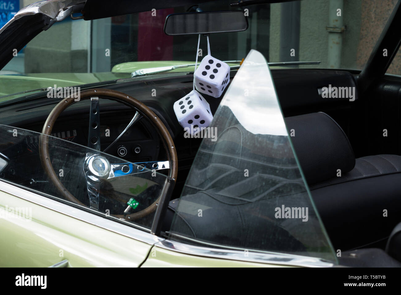 Fuzzy Dice on the rearview mirror of a vintage American car - Stock Image