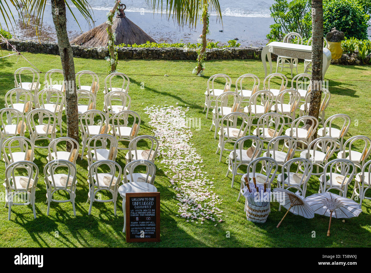 Wedding arch, chairs and umbrellas for guests among palm trees near the ocean. Blackboard sign saying to turn cell phones off for unplugged ceremony. - Stock Image