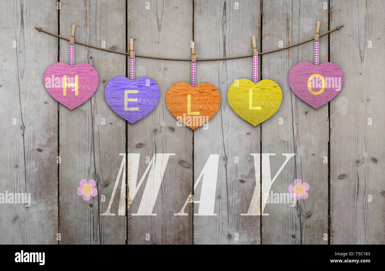 Hello May written on hanging pink and orange and purple hearts and weathered wooden background, with flowers Stock Photo