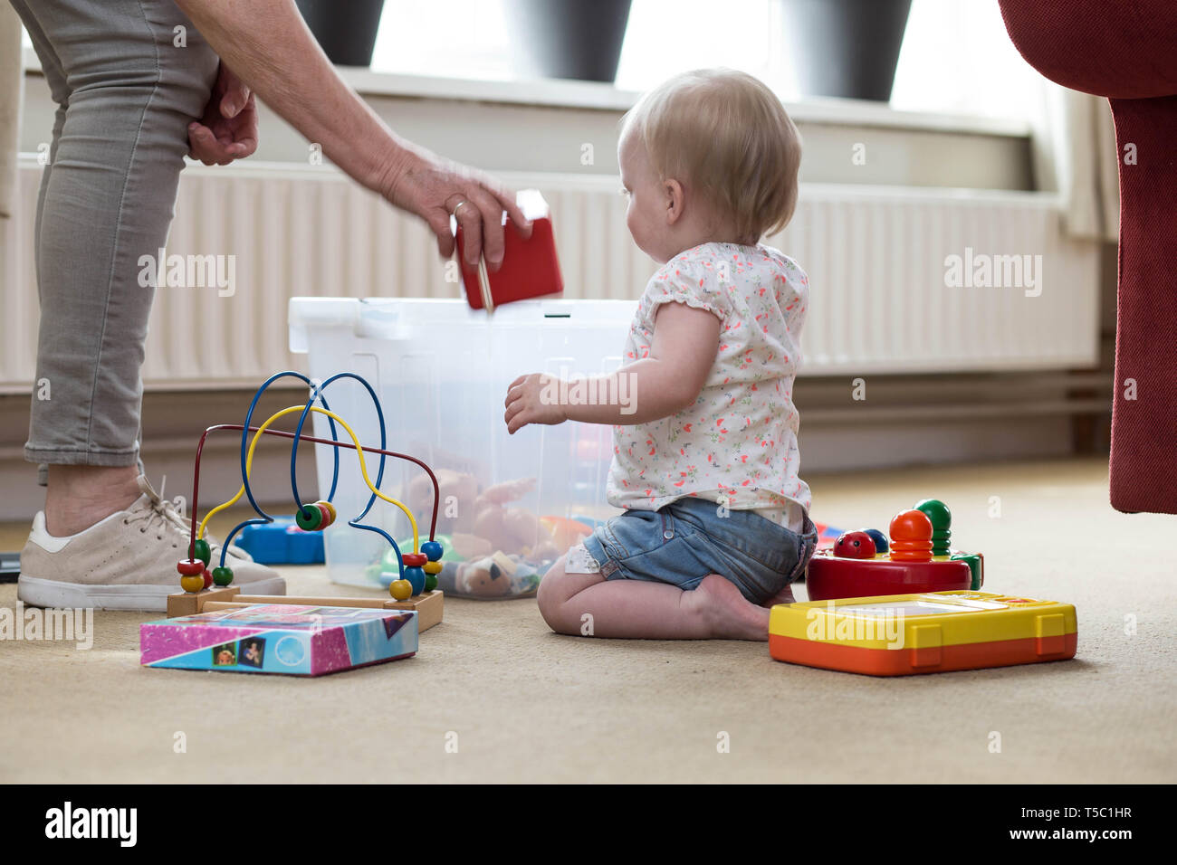 Grandma and baby with toys on the floor in livingroom - Stock Image