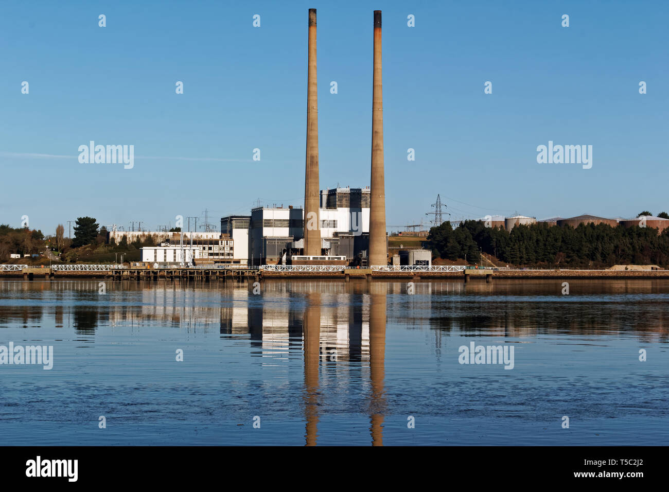 Image of a power plant with two chimneys on Little Island in Waterford Harbour,Ireland. - Stock Image