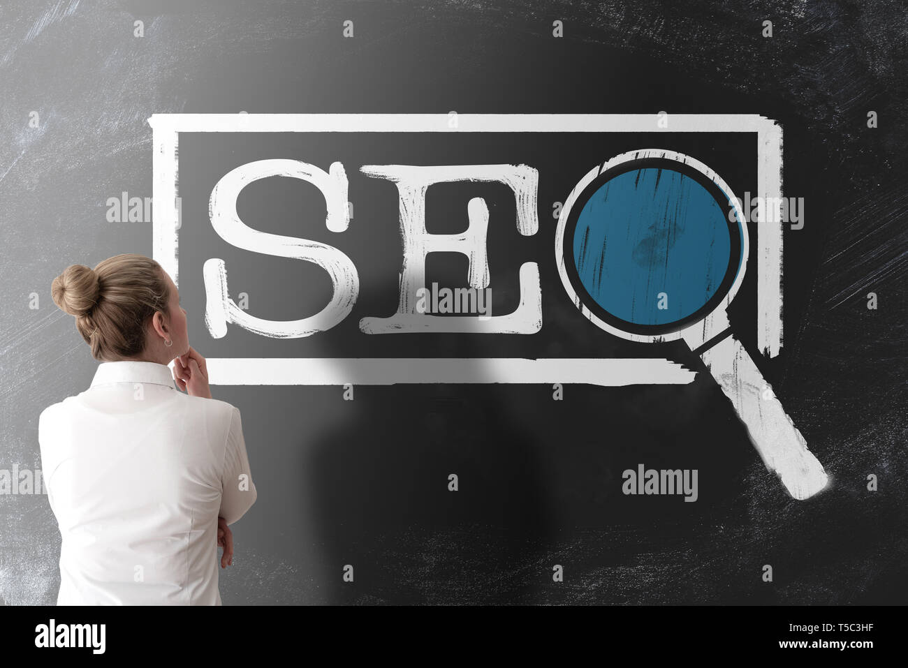 rear view of woman in white blouse looking at term SEO, search engine optimization,  on chalkboard Stock Photo