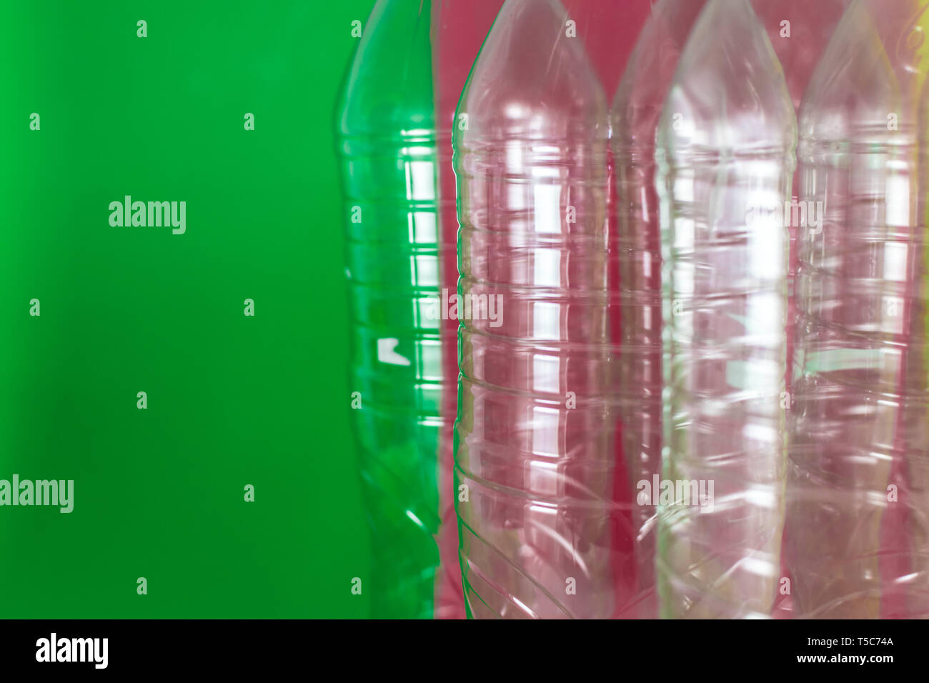 A pack of empty and recyclable plastic water bottles, on a colored vibrant green and wine red background. Reuse, Eco-Friendly, Environment concept - Stock Image