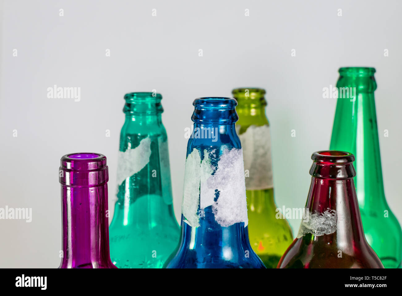 Image of the bottleneck of empty colored beer and wine glass bottles on a white background. Green, yellow, pink and blue colours. Reuse, acoholism - Stock Image
