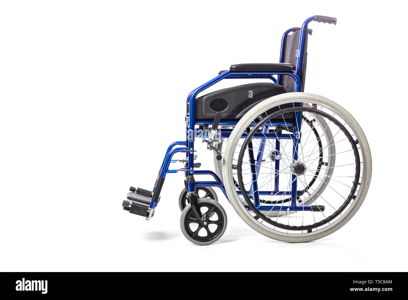 Detail of a classic wheelchair for physical disability on a white background. Concept of hospital care and disability, side view - Stock Image