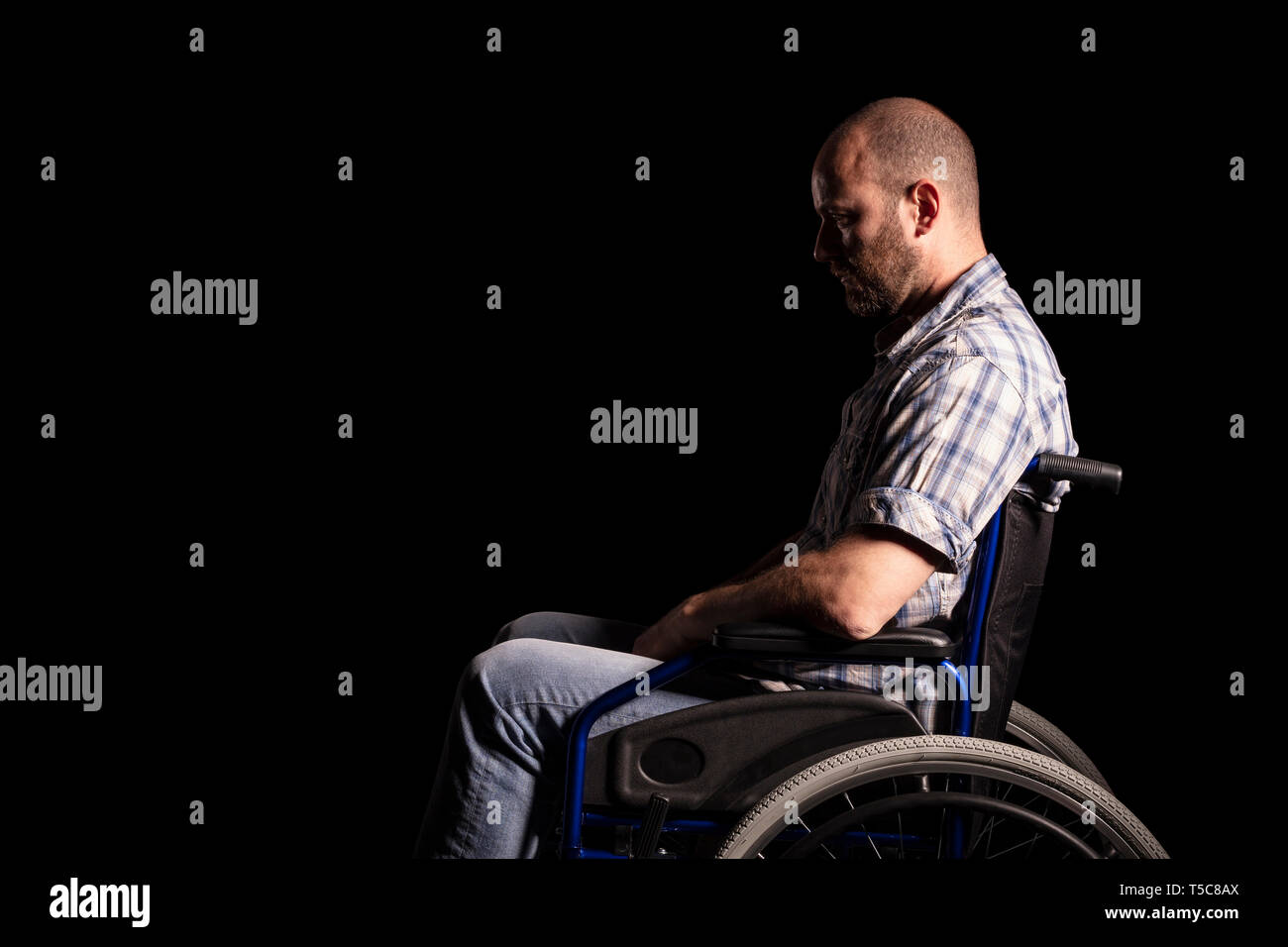 Portrait of caucasian man sitting in a wheelchair, sad and thoughtful expression. Black background. Concept of patient and physical disability. - Stock Image