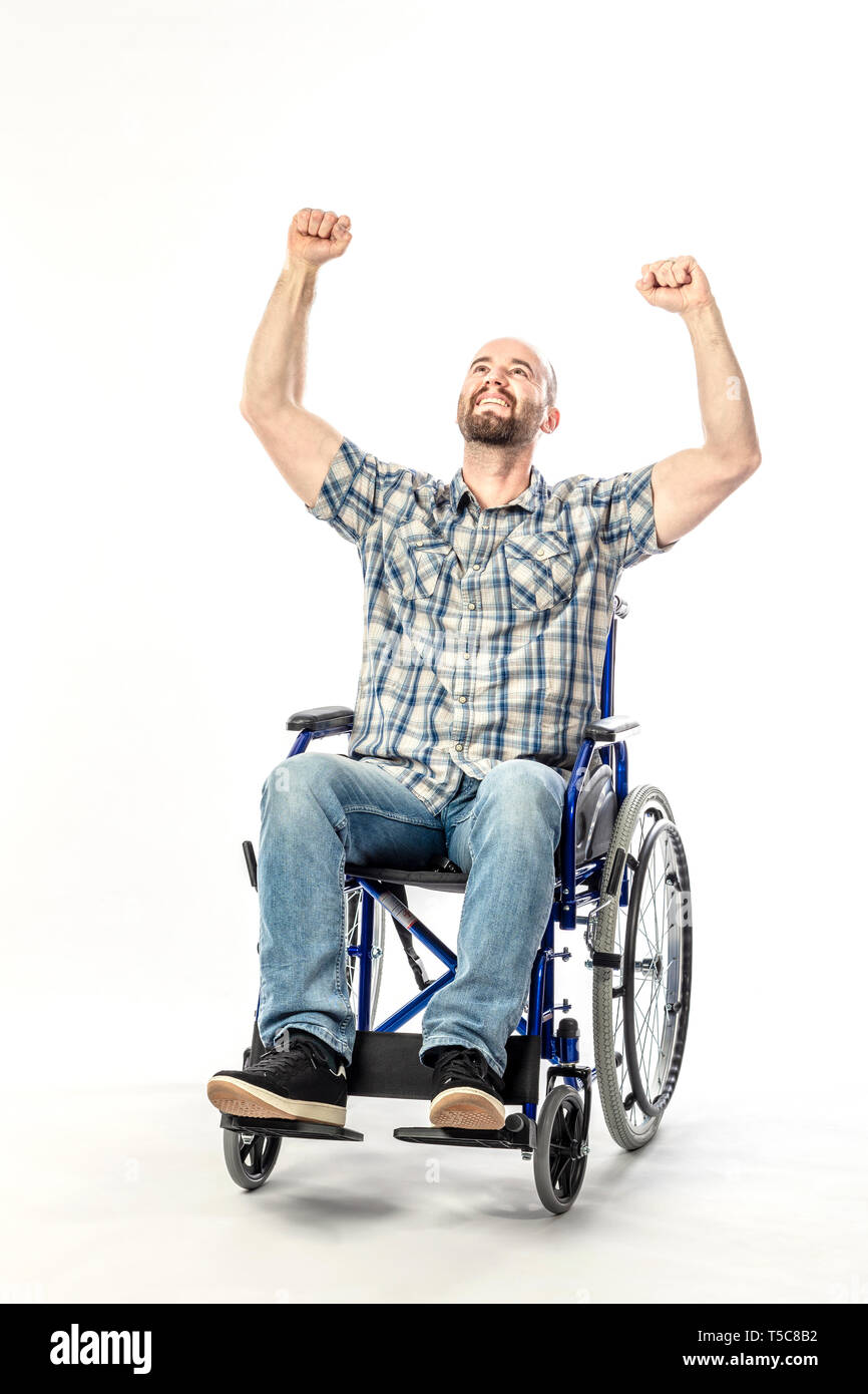 Man in wheelchair smiling and with arms raised as a sign of victory. Concept of disability and positive thinking. - Stock Image