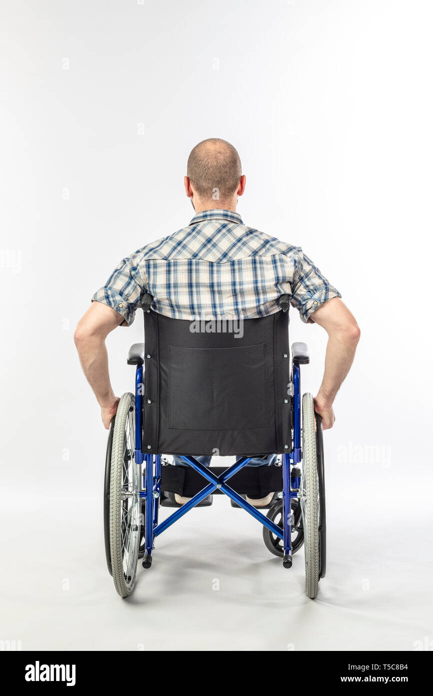 Man sitting on a wheelchair because he is injured. white background and back view. Concept of disability and medical support. - Stock Image