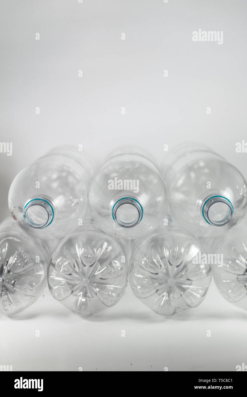 Pile of pack of a liter and a half of empty mineral water without caps just with the blue sealing ring on a white background, and space for inserts - Stock Image