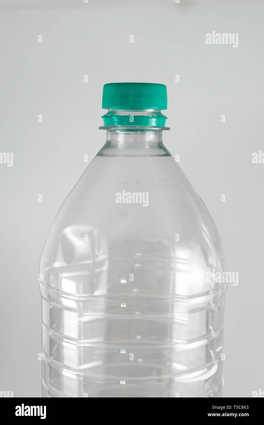 Bottleneck of a empty bottle of a liter and a half of mineral water with sea green cap and sealing ring on a white background, and space for inserts - Stock Image