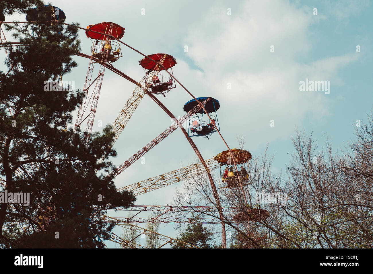 ferris wheel on a background of clouds in the city - Stock Image
