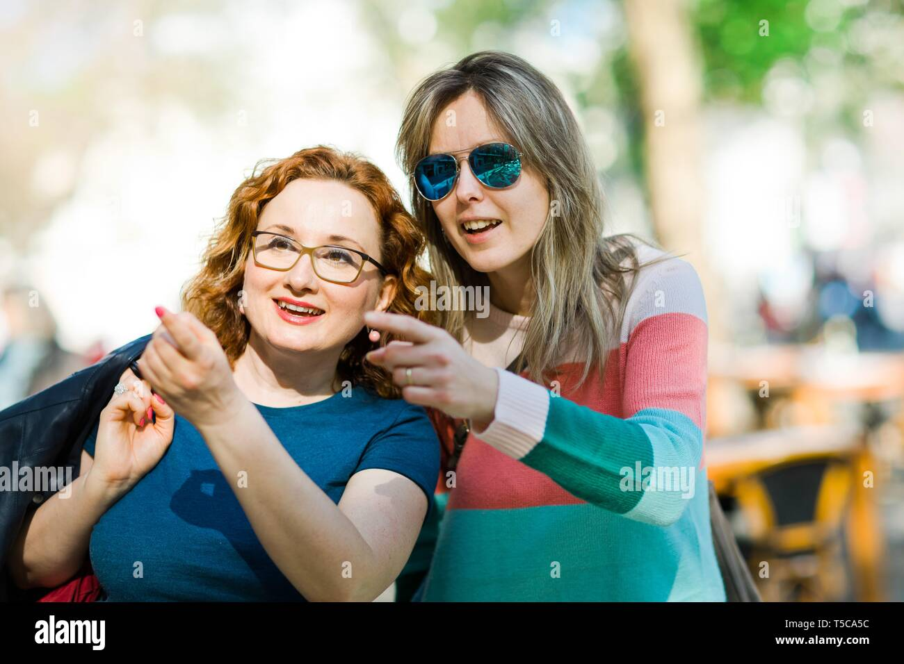 Two women surprisingly pointing to interesting places over the city, showing important places. - Stock Image