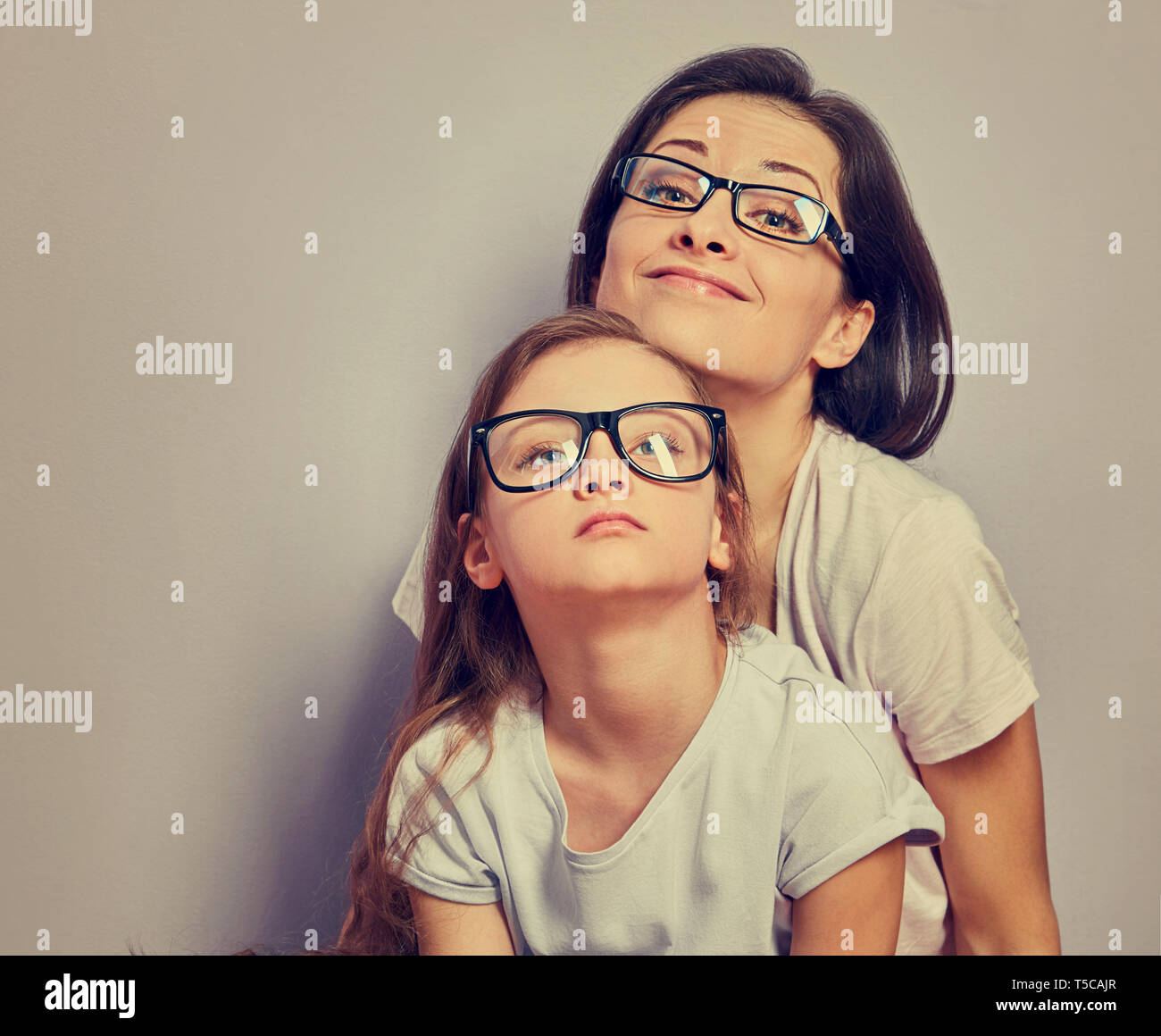Grimacing positive smiling casual mother looking sitting with her unhappy offended thinking kid girl on violet wall background. Family in fashion eye  - Stock Image
