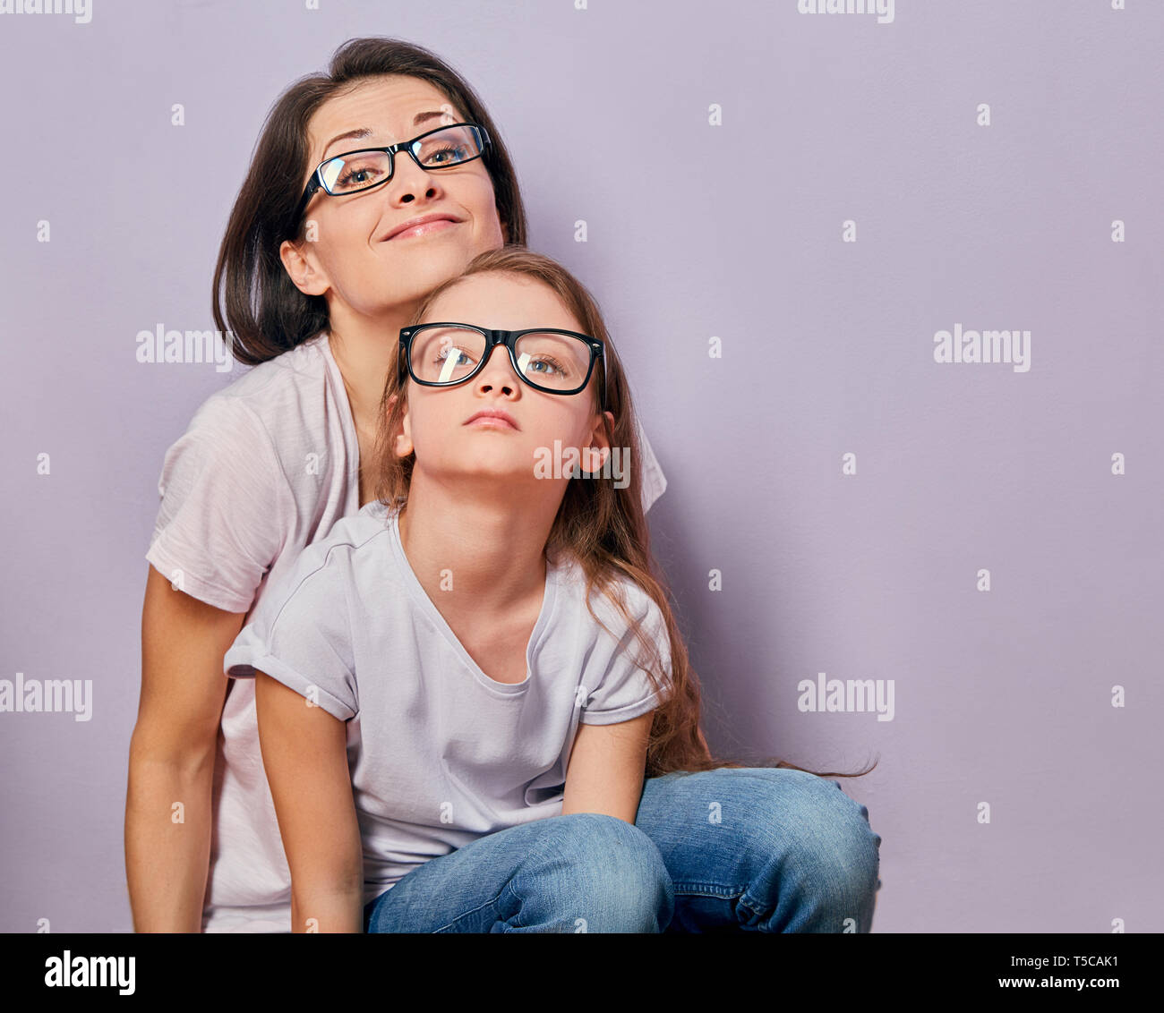 Grimacing positive smiling casual mother looking sitting with her unhappy offended thinking kid girl on violet wall background. Family in fashion eye  Stock Photo