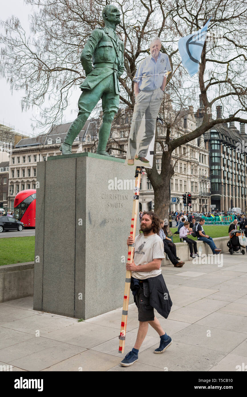 An image of veteran wildlife and environmental broadcaster Sir David Attenborough is held high in Parliament Square next to the statue of Field Marshal Jan Christiaan Smuts, the South African and British Commonwealth statesman, military leader and philosopher, during the week-long protest by climate change activists with Extinction Rebellion's campaign to block road junctions and bridges around the capital, on 23rd April 2019, in London England. Stock Photo