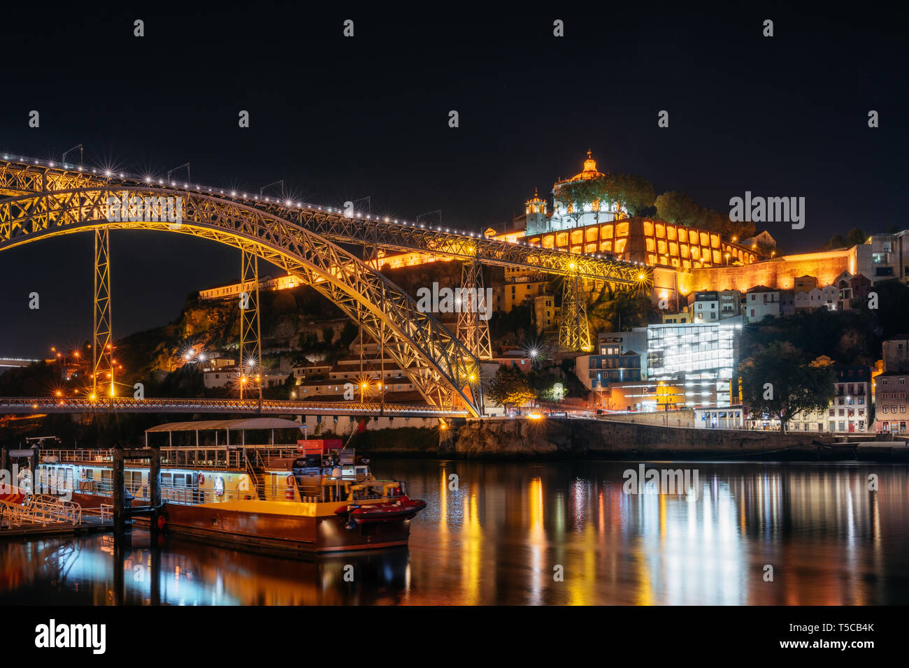 Dom Luis I bridge, medieval monastery fort Mosteiro da Serra do Pilar and boat with illumination, Porto old town, Portugal - Stock Image