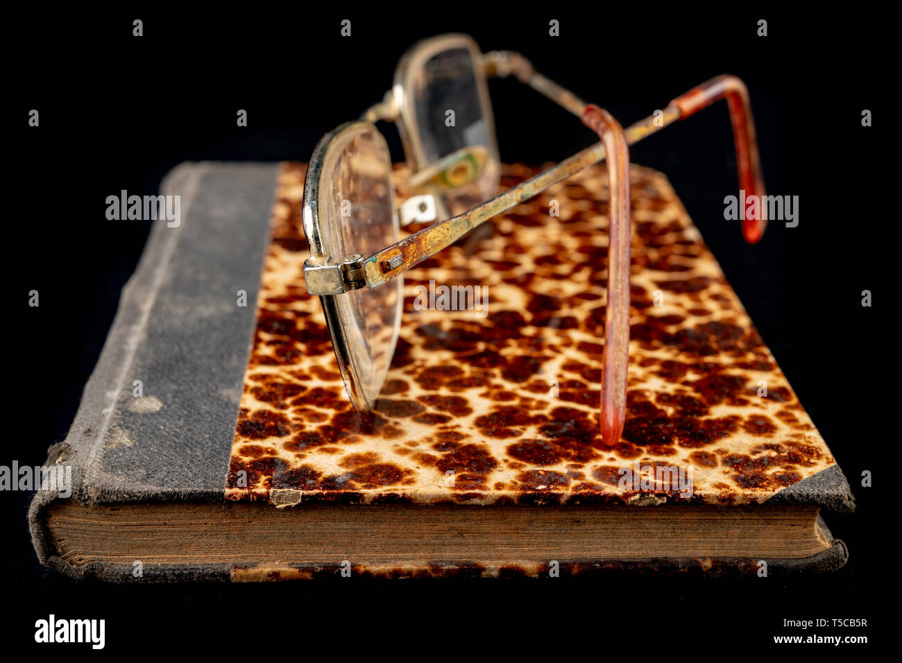 Old book and glasses on a dark wooden table. Forgotten publishing in binding from several decades ago. Black background. - Stock Image