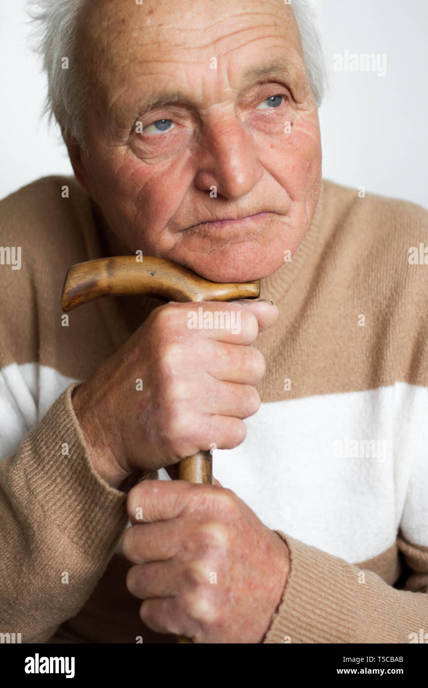 Portrait of an old sad man who put his head on the handle of a wooden cane, the concept of loneliness at home. Stock Photo