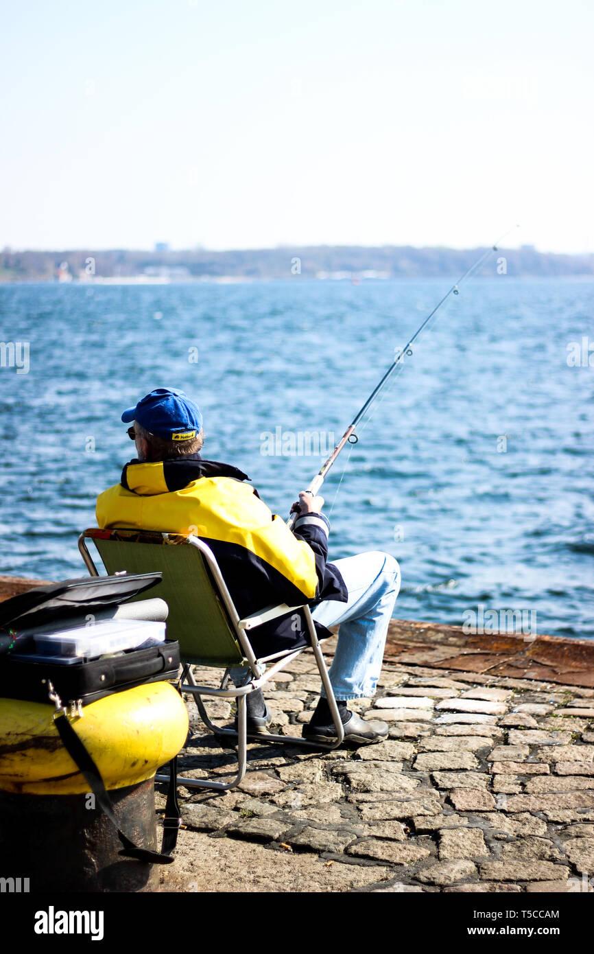 Fischersmann in schwarz-gelber Jacke sitzt an Kieler Förde mit Angel und fängt Fische - Stock Image