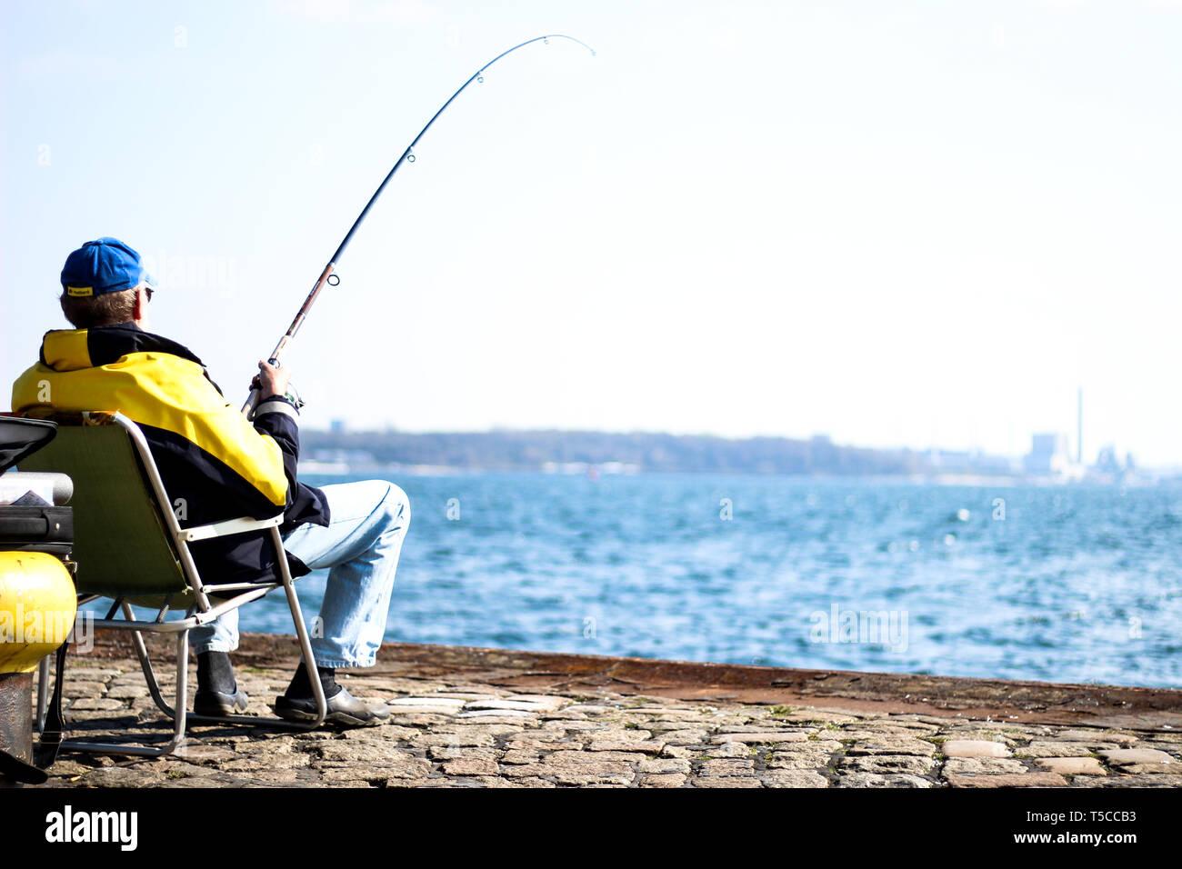 Fischersmann in schwarz-gelber Jacke sitzt an Kieler Förde mit Angel und fängt Fische Stock Photo
