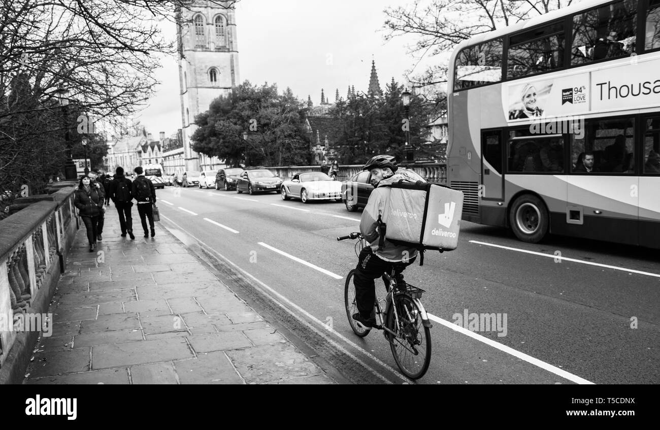 Oxford, United Kingdom - Mar 3, 3017: Black and white young male cyclist delivering food fast to client via Deliveroo App - commuting fast in the university city with big thermo bag with Deliveroo logo - Stock Image