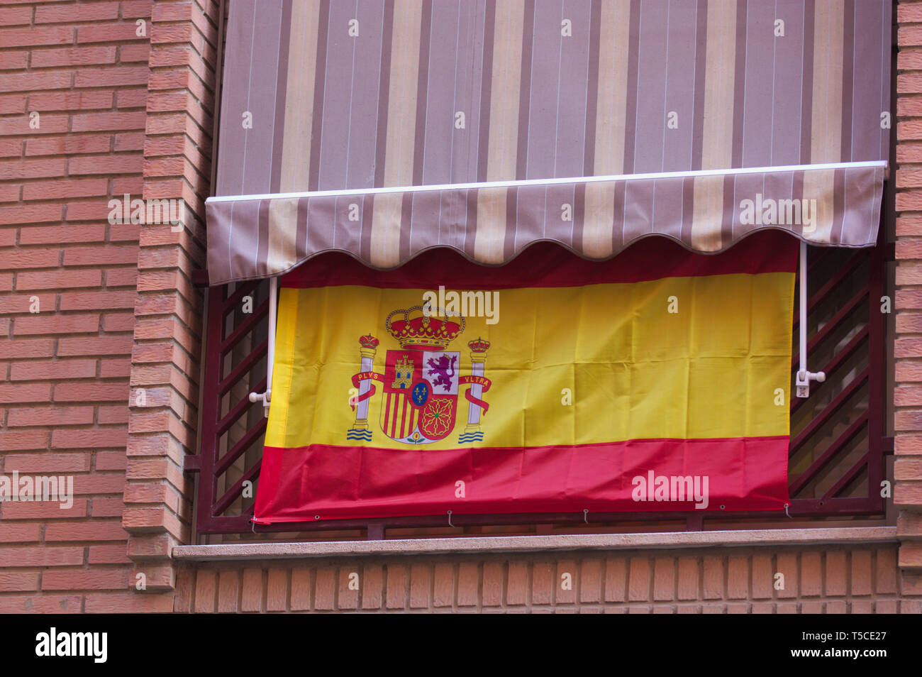 Spanish flag hanging from a balcony in a Spanish state city to indicate Spanish national patriotic fervor - Stock Image