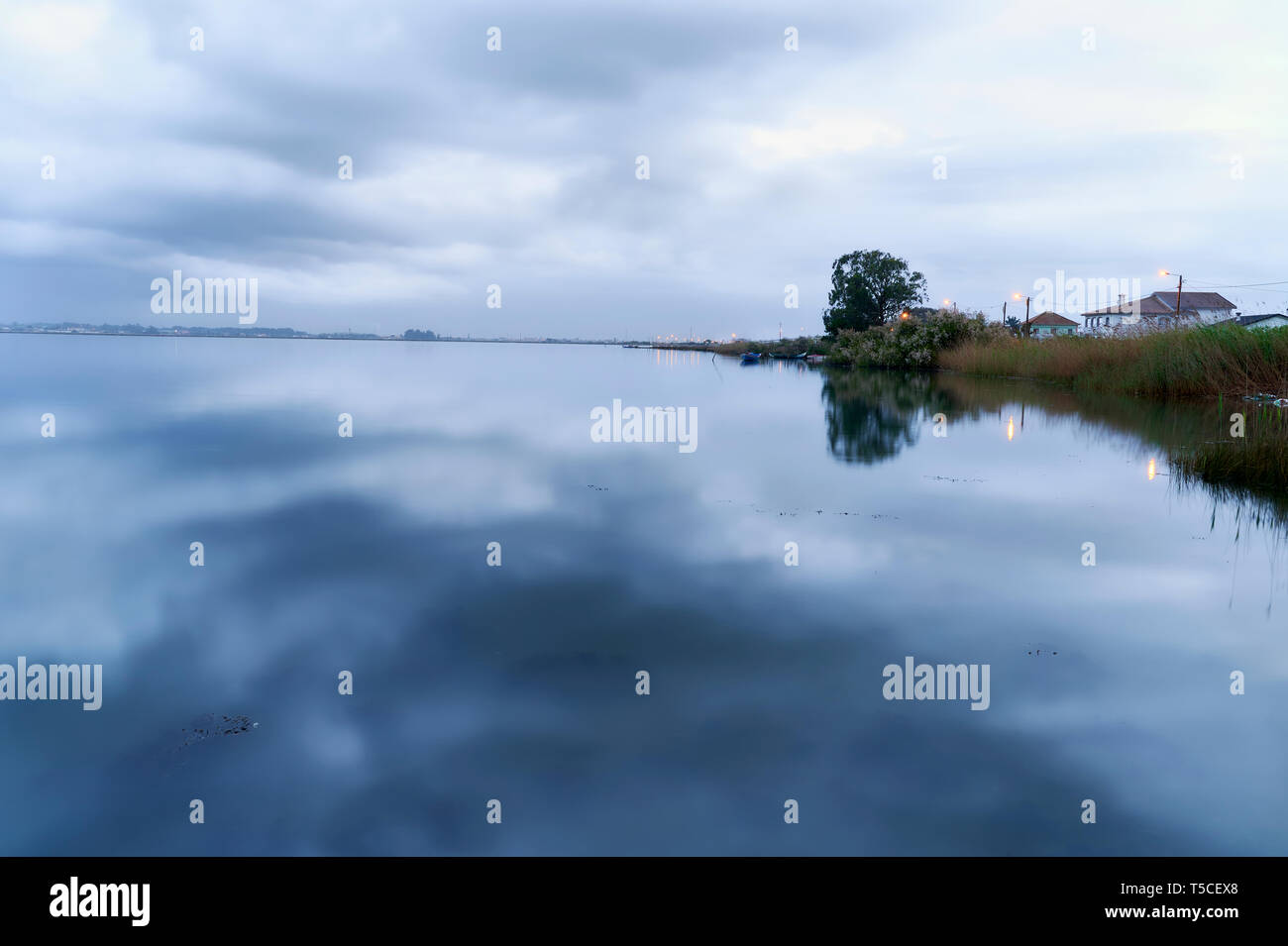 Shore and cloudy winter sky, are reflected in the lake surface ant blue hour in Torreirra, Aveiro Lagoon, Portugal Stock Photo