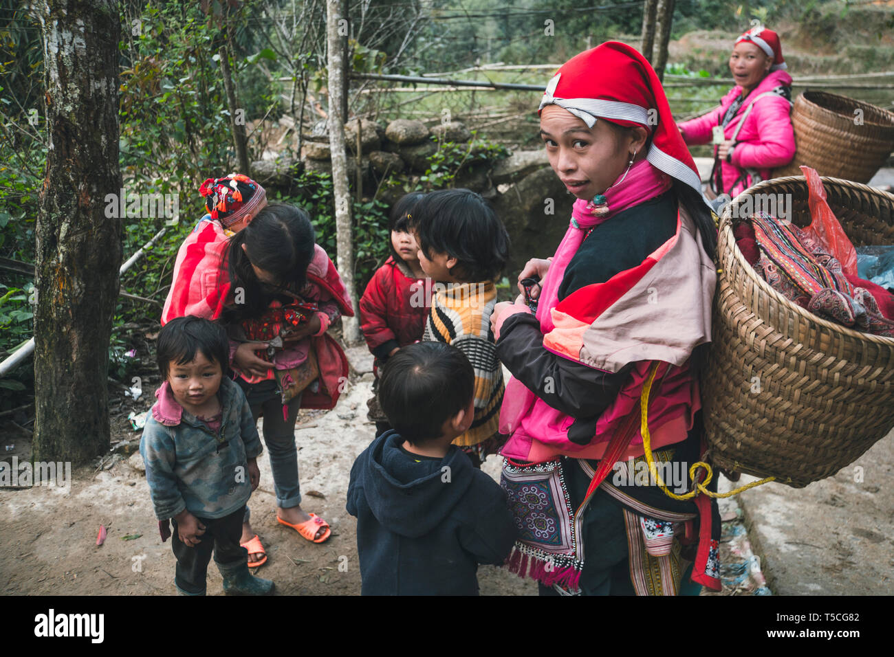 girl from the tribe red dzao, with a large wicker basket behind, surrounded by children. TA PHIN, LAO CAI, VIETNAM - 12 January 2019 Stock Photo